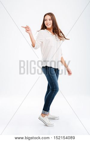 Full length portrait of a happy casual woman pointing finger away isolated on a white background