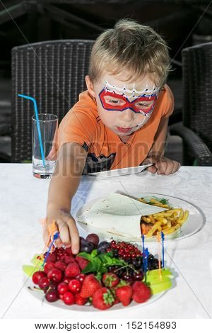 Young boy with painted face reaching for fruit