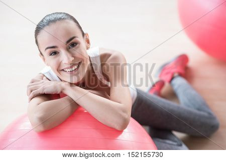Positive emotions. Beautiful elated positive woman leaning on a fitness ball and smiling while being in the sports hall