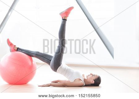 Fitness exercise. Well built slender young woman resting one leg on a fitness ball and holding the second one up while lying on the floor