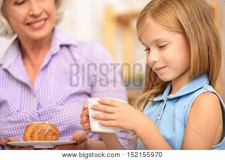 Cute girl is drinking tea with her grandmother. She is sitting and holding cup with joy. Mature woman is carrying plate with pastry and smiling