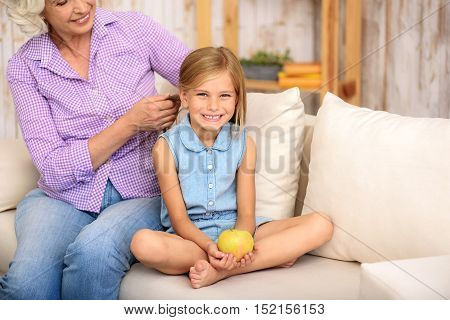 Kind grandmother is braiding her granddaughter hair with joy. Little girl is looking at camera with happiness and laughing. She is sitting on sofa and holding apple