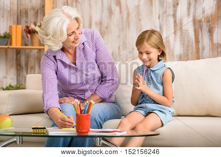 Kind grandmother is teaching her granddaughter to draw. She is holding a pencil and smiling. Girl is sitting on sofa and looking at picture with interest