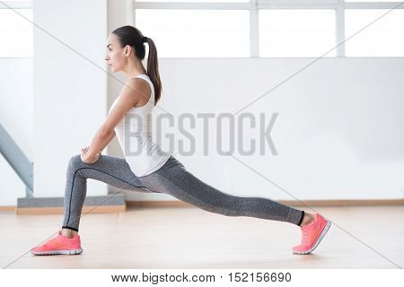 Physical activities. Serious nice active woman doing a physical exercise and concentrating on the activity while being in a fitness hall