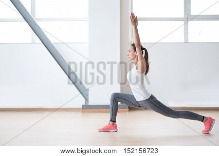 Fitness workout. Well built confident active woman holding her hands up and looking forward while standing in a special position