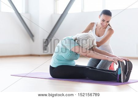 Sport needs hard work. Pleasant determined active woman sitting on a yoga mat and leaning forwards while exercising with a coach