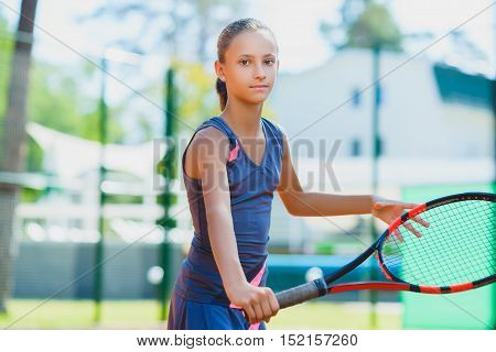 Smiling Children playing tennis and posing indoor.