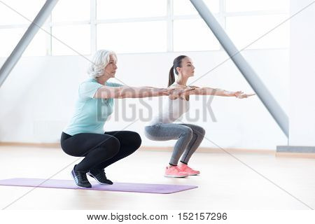 Synchronous movements. Nice serious slender women stretching out their arms and squatting while training