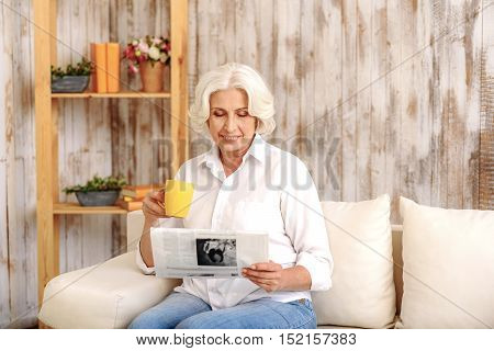 Happy old woman is reading newspaper and smiling. She is sitting on sofa and drinking tea