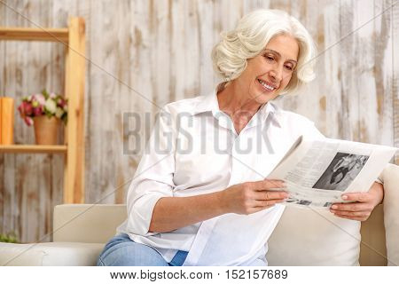 Happy old woman is reading newspaper at home. She is sitting on couch with relaxation and laughing