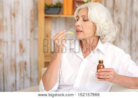 Sick old woman is taking cough syrup wit concentration. She is sitting on sofa at home