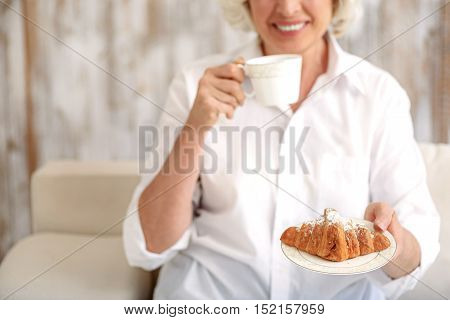 Joyful old woman is drinking coffee and stretching croissant to camera. She is sitting on sofa and smiling