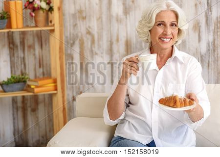 Happy old woman is inviting to tea party. She is proposing pastry and smiling. Woman is sitting on couch and holding cup
