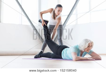 Intensive training. Nice slim grey haired woman holding her leg up and smiling while lying on the yoga mat