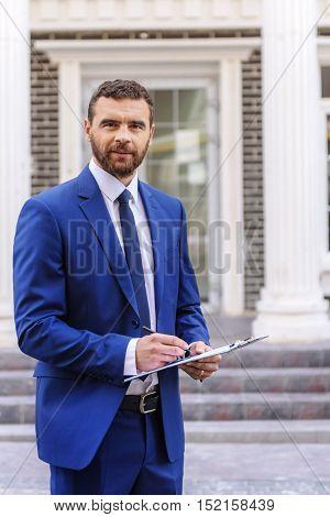 handsome realtor in a luxurious suit standing in front of the street door