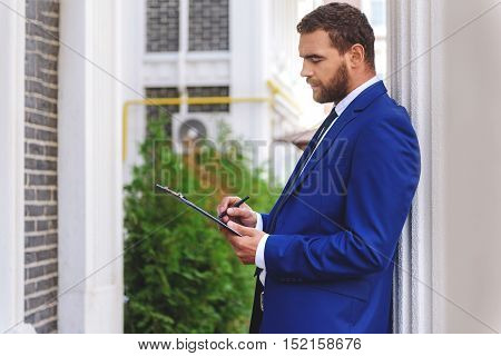 elegant inspector in a costume writing in front of a house