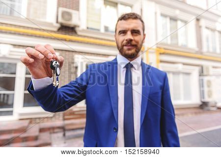 you will be a homeowner, happy handsome realtor holding keys to the house in hands against buildings
