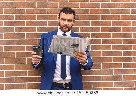 smart man reading the newspaper and drinking coffee against the brick wall background