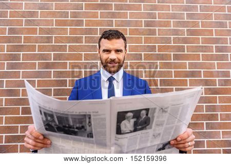successful lawyer in a suit holding newspaper against the brick wall