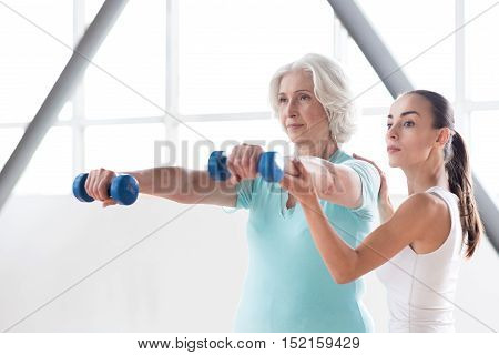 Develop your body. Serious confident persistent woman standing near the coach and looking forward while holding blue dumbbells in front of her