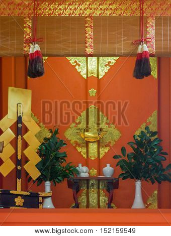 Kyoto Japan - September 17 2016: Altar of small shrine at Fushimi Inari Taisha Shinto Shrine offers a dominant vermilion color with golden decorations white vases and green leaves.