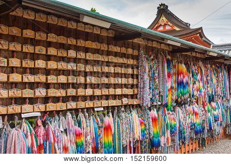 Kyoto Japan - September 17 2016: Wall of prayers and wishes left at Fushimi Inari Taisha Shinto Shrine. Wooden boards and colorful strings of origami cranes each holding a prayer.