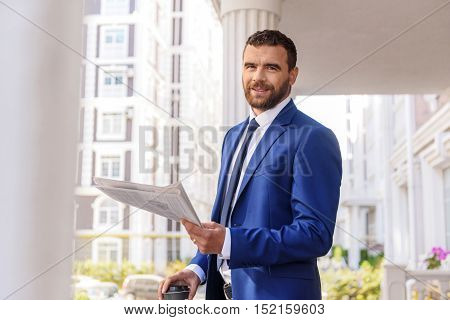 successful modern man with newspaper standing on a terrace and looking into a camera
