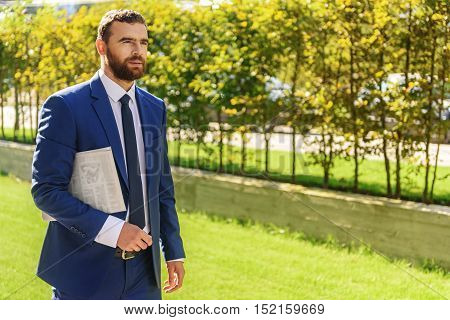 handsome man in a suit walking on a sunny day with a newspaper under arm
