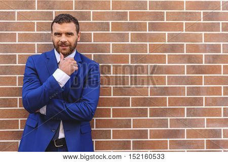 elegant cheerful boss in the expensive suit standing in front of the wall with copy space, success concept