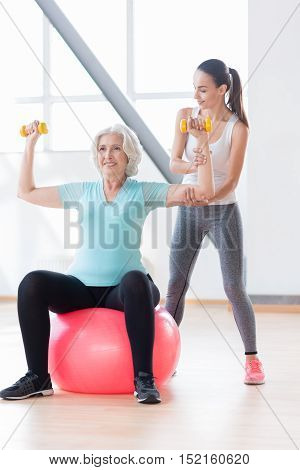 Build up your muscles. Good looking happy old woman holding yellow dumbbells and exercising with them while sitting on a fitness ball
