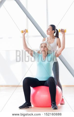 Serious attitude to the workout. Persistent confident active woman sitting on a fitness ball and raising her arms while holding dumbbells