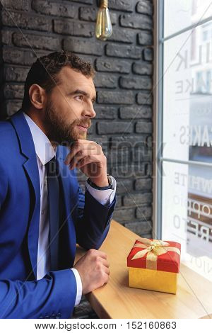 thoughtful man sitting with a gift in a cafe