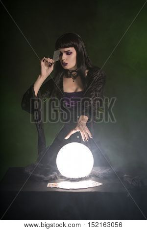 Attractive fortune teller with playing cards and crystal ball, Halloween theme