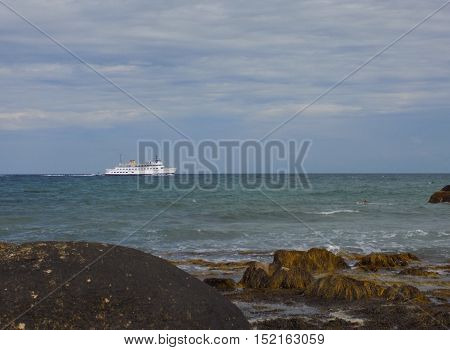 ferry passing beach with rocks through ocean waters