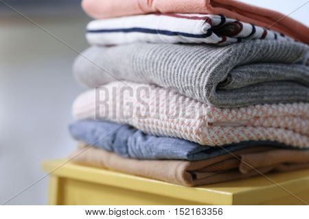 Pile of clothes on yellow stool