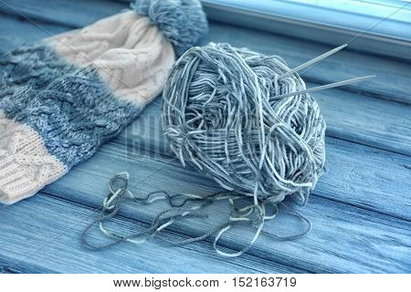 Knitted cap, ball of yarn and needles on wooden surface