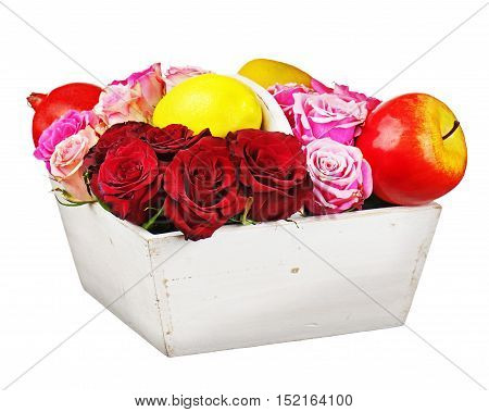 Flower arrangement of red roses and fruits in wooden basket isolated on white background. Closeup.