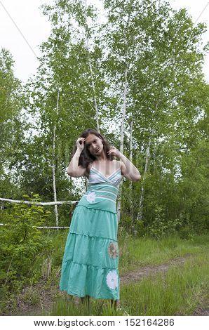 A girl in a long sundress standing in a birch grove