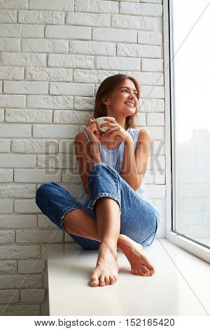 Delighted young girl is thinking and looking out of the window while sitting on the window-sill and drinking a cup of aroma coffee