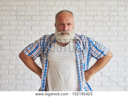 Happy stylish senior dressed in jeans and checkered shirt and holding hands on his hips, white brick wall in background