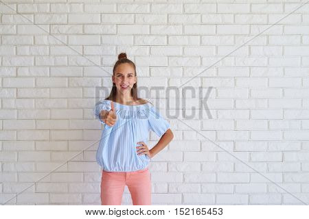 Close-up portrait of a cute girl showing thumb up standing against white background