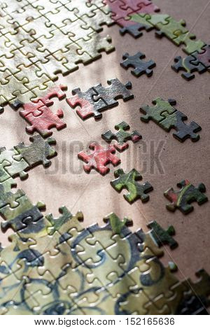 Partially completed jigsaw puzzle on table closeup