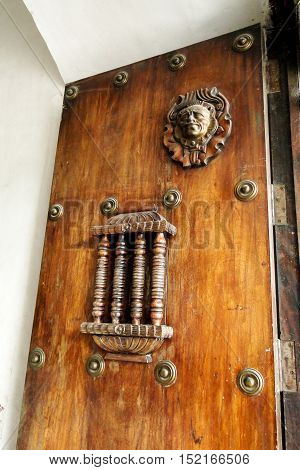 Rustic door with iron bar window and a lion head emblem with old bolts