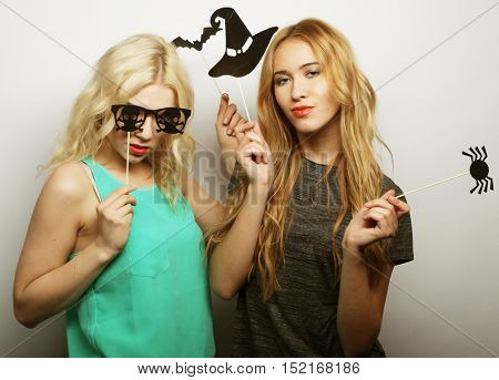 two stylish sexy hipster girls best friends ready for party, over gray background