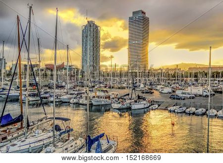 BARCELONA SPAIN - JULY 13 2016: Yachts and sailboats moored in the Port Vell of Barcelona with view to Skyscrapers Torre Mapfre