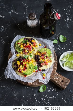 Spicy bean tostadas with corn salsa and avocado and beer on a dark background.