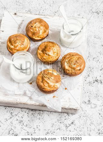 Pumpkin and cream cheese swirl muffins and greek yogurt. Delicious breakfast or snack. On a light background