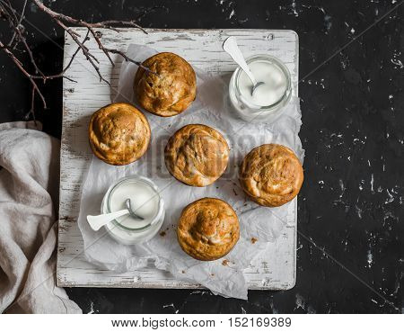 Pumpkin and cream cheese swirl muffins and greek yogurt. Delicious breakfast or snack. On a dark background top view. Rustic style