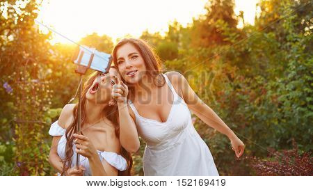 Two cute sisters make fun selfie. Girls fooled. They are singing. Family fun.