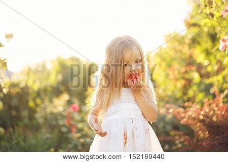 Nice little girl eating a tomato. She stands barefoot on the green lawn. Girl soiled white dress in tomato juice.
